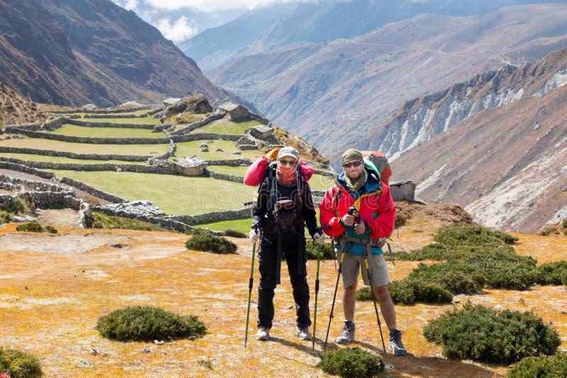 Соедините backpackers туристов стоя деревня фермы горы, Nep стоковое изображение