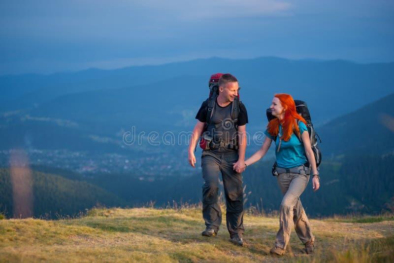 Соедините hikers при рюкзаки держа руки, идя в горы стоковое фото