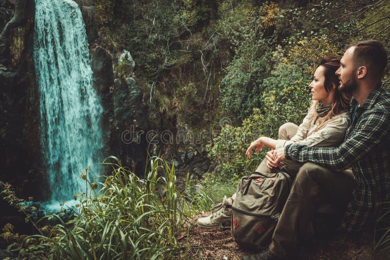 Соедините hikers сидя около водопада в глубоком лесе стоковое фото rf