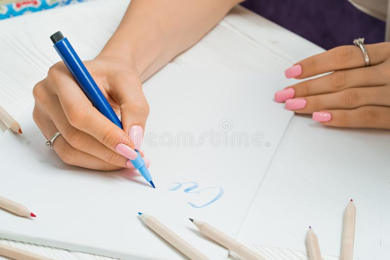 создайтесь Женская рука пишет красивые голубые письма на холсте в красочной рамке ручек Сценарий каллиграфии Искусство сочинитель стоковое фото rf