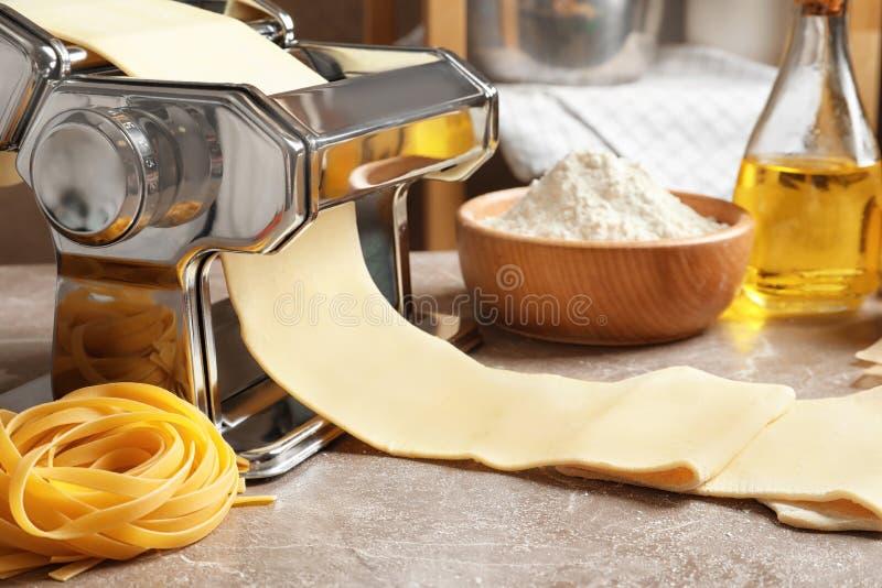 Создатель макаронных изделий с тестом на кухонном столе стоковое изображение