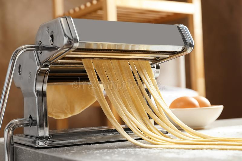 Создатель макаронных изделий с тестом на кухонном столе стоковые фото