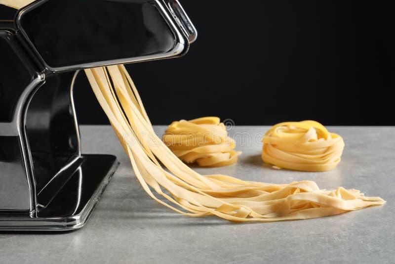 Создатель макаронных изделий с тестом на кухонном столе стоковое фото
