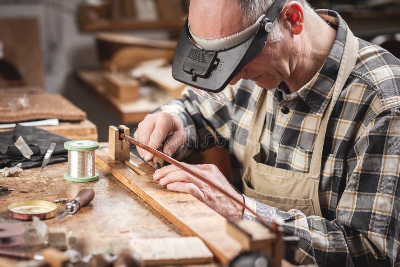 Создатель скрипки внутри деревенской мастерской работает на смычке с точностью стоковые изображения rf