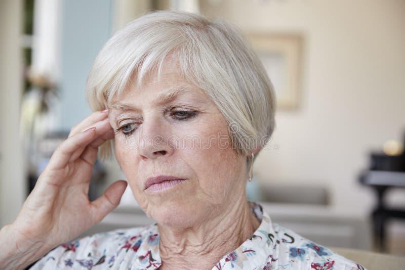 Созерцательная старшая женщина дома, близко вверх стоковое фото