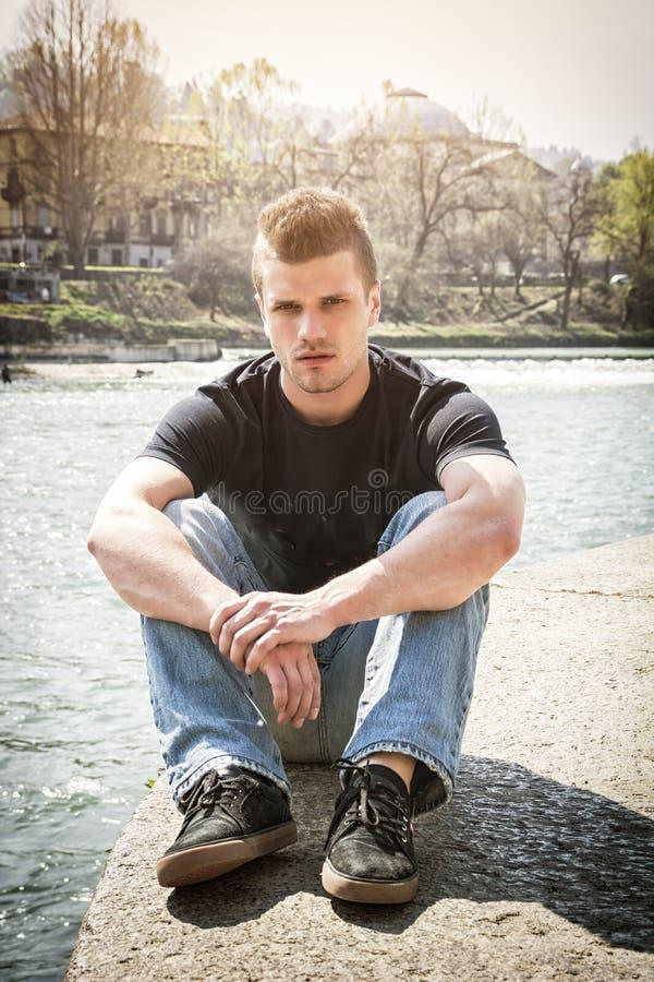 Созерцательный молодой человек сидя около реки в Турине стоковые фотографии rf