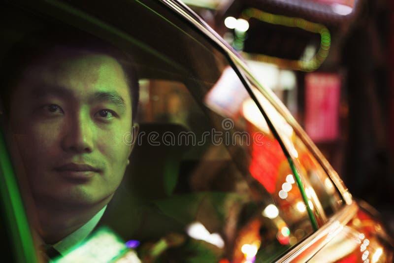 Созерцательный бизнесмен в заднем сиденье автомобиля смотря вне через окно на ноче, Пекине стоковые фотографии rf