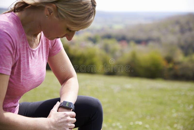 Созрейте женщина проверяя отслежыватель деятельности пока на беге стоковое фото rf