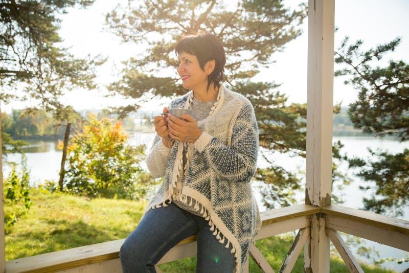 Созрейте привлекательная женщина стоя на террасе с чашкой горячего кофе стоковые фото