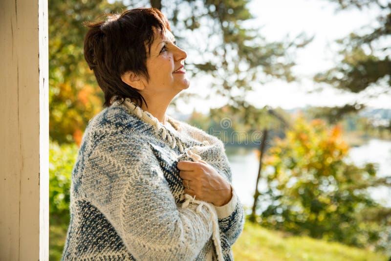 Созрейте привлекательная женщина стоя на террасе с чашкой горячего кофе стоковые изображения