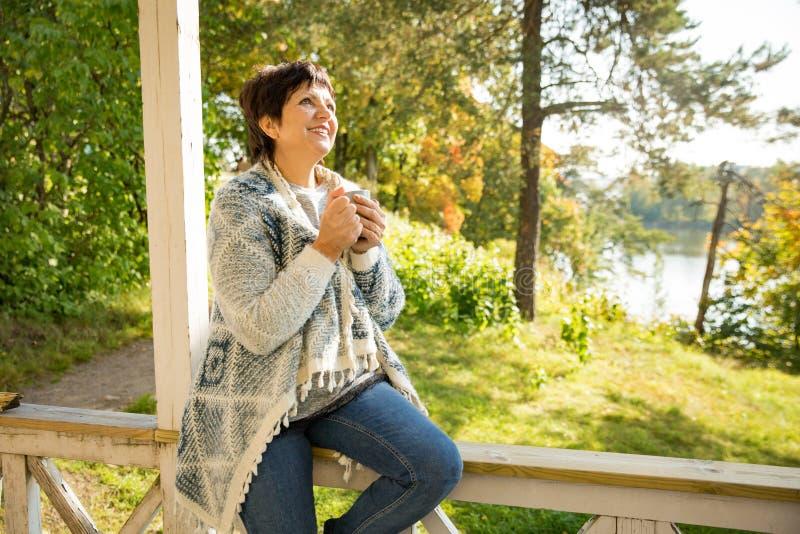 Созрейте привлекательная женщина стоя на террасе с чашкой горячего кофе стоковые изображения rf