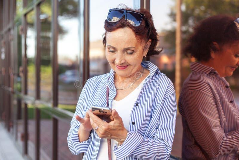 Созрейте привлекательная стильная женщина выбытая используя мобильный телефон app стоковые изображения rf