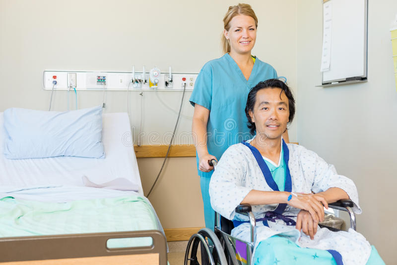 Созрейте терпеливое усаживание на кресло-коляске пока медсестра стоковое изображение