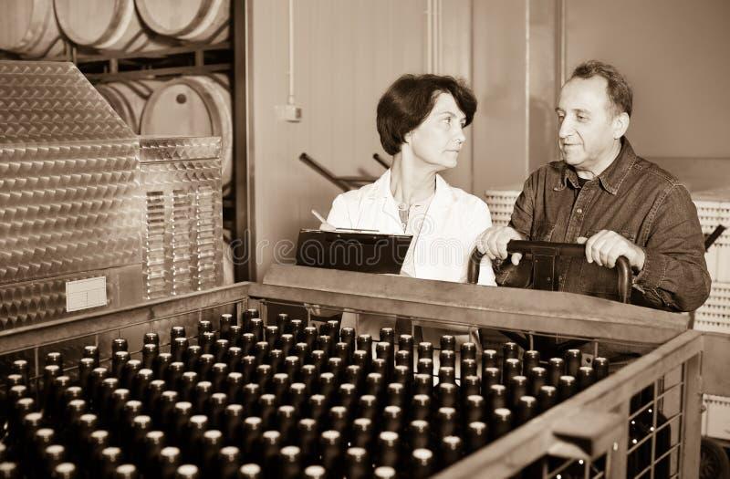 Создатель вина показывая бутылки с вином стоковые фотографии rf