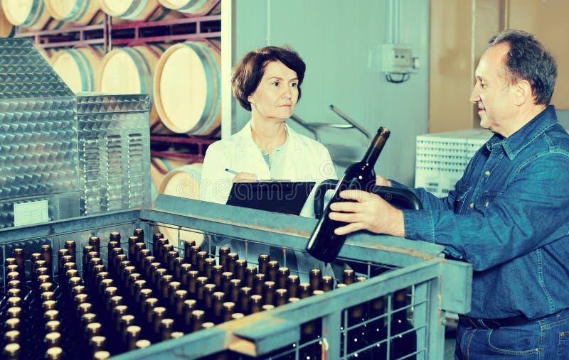 Создатель вина показывая бутылки с вином стоковое изображение rf