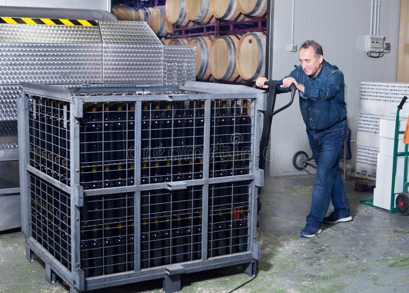 Создатель вина разгржает контейнеры с бутылками стоковые фото