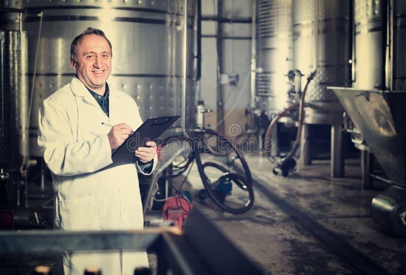 Создатель вина рассматривает оборудование на винодельне стоковые изображения rf
