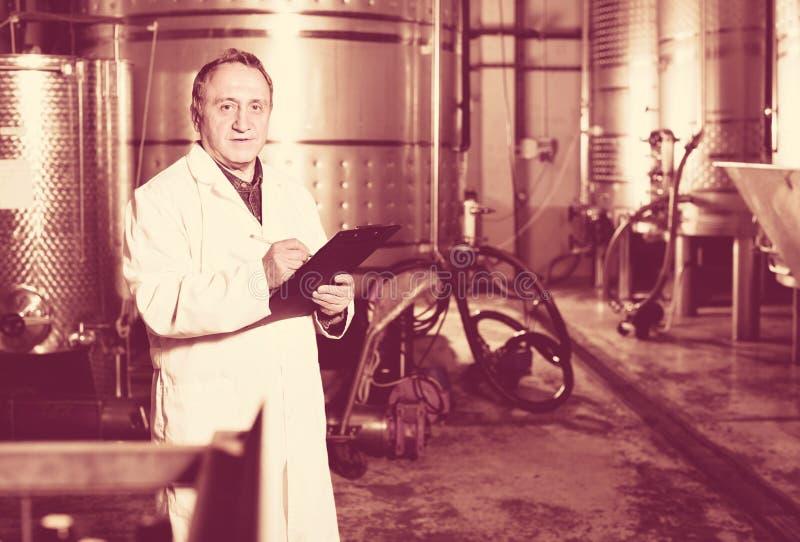 Создатель вина рассматривает оборудование на винодельне стоковое фото