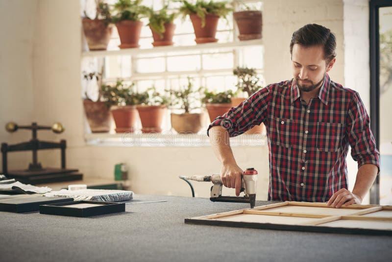 Создатель используя инструмент работы для того чтобы обрамить художественное произведение стоковое фото rf