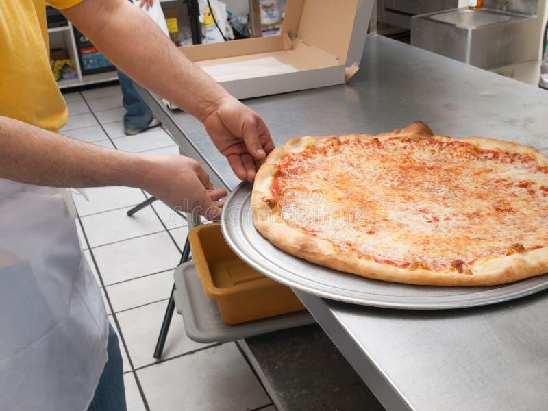 Создатель пиццы извлекает свежую пиццу от печи стоковые фото