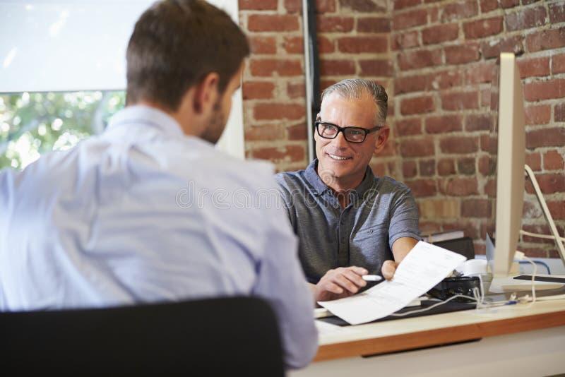 Соискатель бизнесмена интервьюируя мужской в офисе стоковые изображения