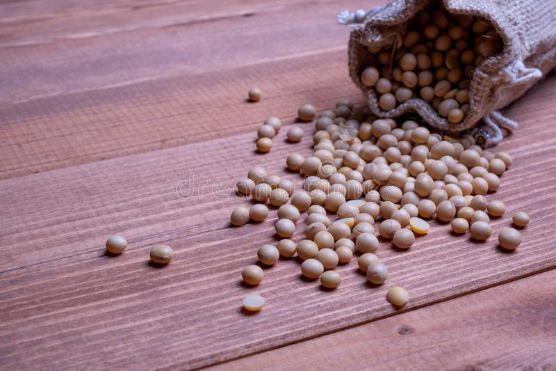 Сои падают из открытой сумки холста на деревянном столе Фасоли сои стоковое фото rf