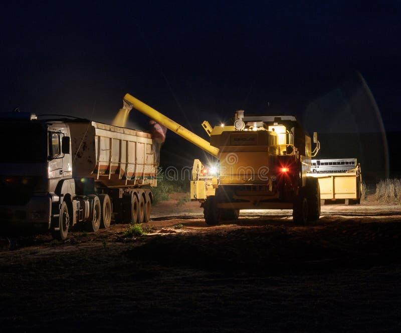 Сои трактора лить на тележке на ноче стоковое изображение