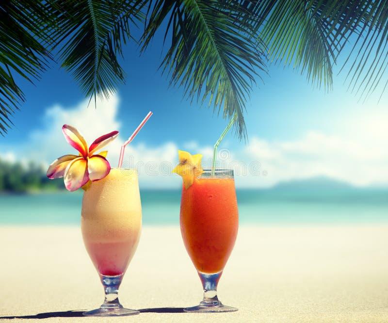 Соки свежих фруктов на пляже стоковые изображения rf