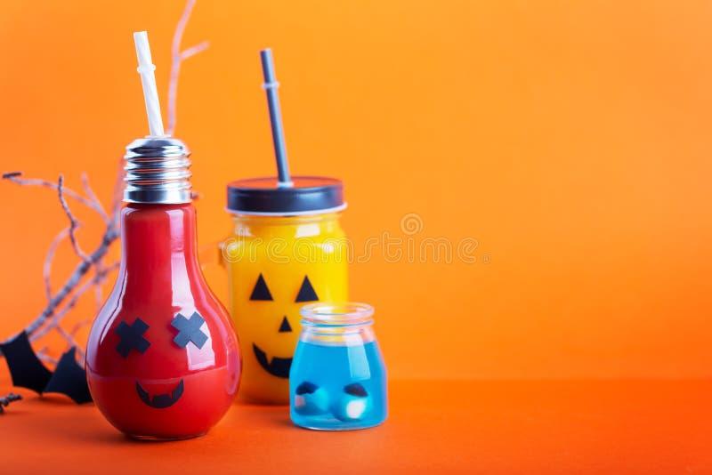 Соки тыквы и томата хеллоуина здоровые в стеклянном опарнике со страшной стороной на оранжевой предпосылке стоковые изображения
