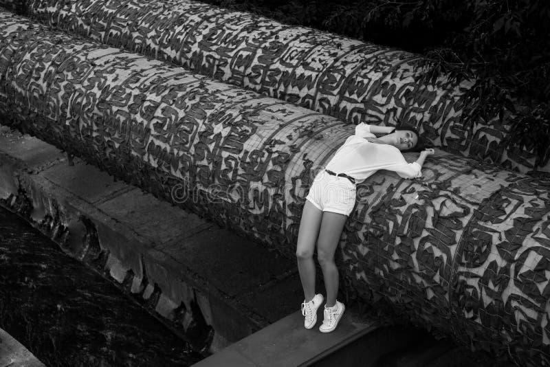 Сокращая женщина в лете одевает лежать на покинутом здании стоковые фото