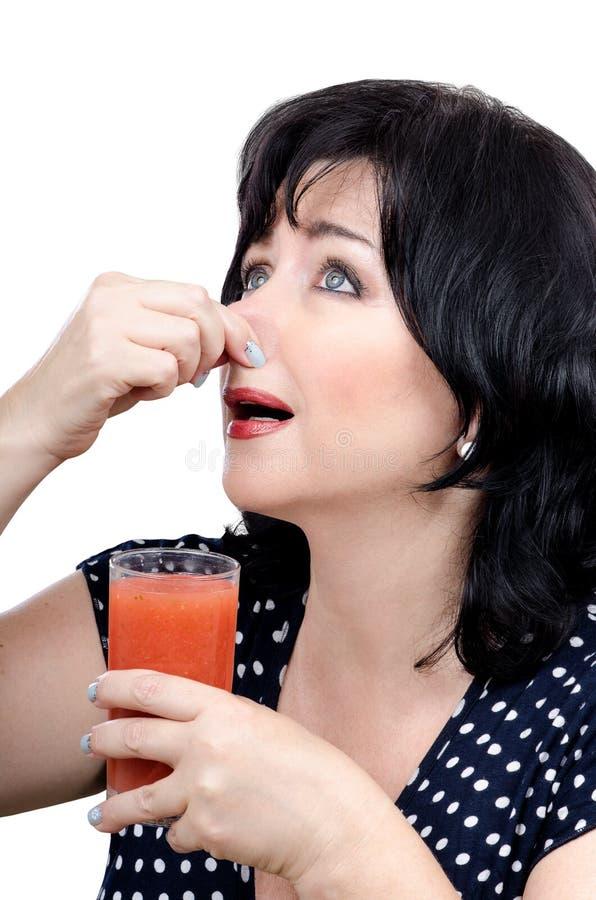 Сок вытрезвителя женщины выпивая в отвращении стоковые фотографии rf