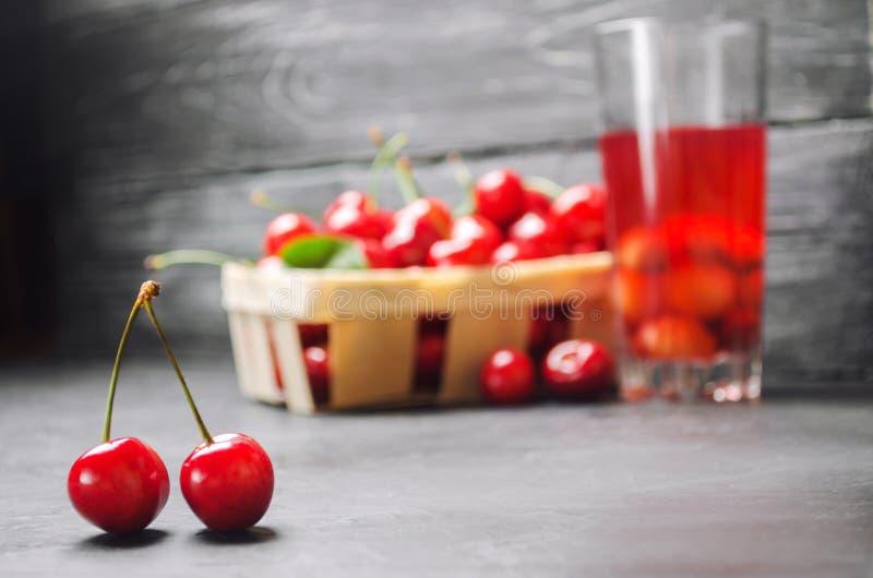 Сок или компот с вишнями свежая зрелая красная вишня в корзине на серой конкретной предпосылке, ягода лета, питье лета стоковые фотографии rf