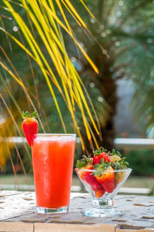 Сок и чашка клубники с естественными свежими клубниками стоковая фотография rf
