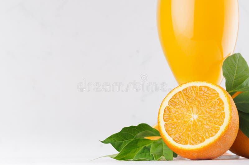 Сок цитруса лета яркий с круглым крупным планом апельсинов куска и молодыми зелеными листьями на белой современной предпосылке стоковые изображения rf