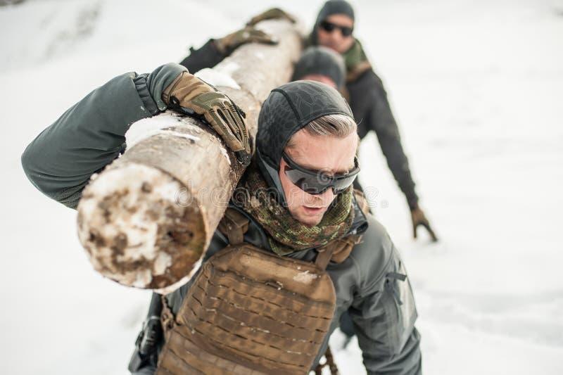 Солдаты армии имеют трудную тренировку с огромной древесиной чурбана стоковое изображение