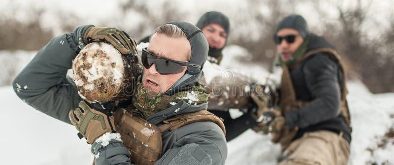 Солдаты армии имеют трудную тренировку с огромной древесиной чурбана стоковые изображения