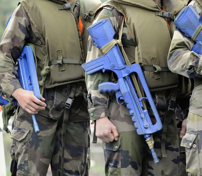 Солдаты с оружи и в форме стоковые изображения