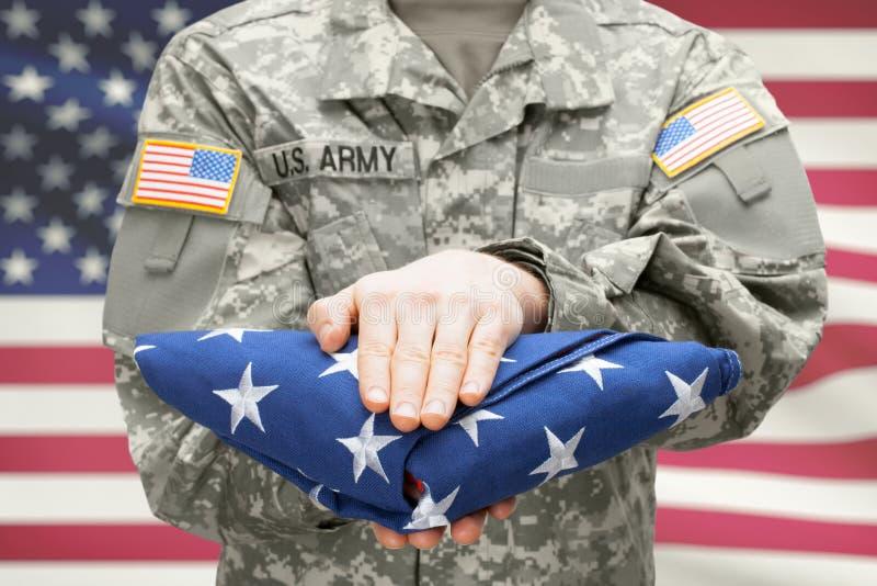 Солдат армии США молодой держа тщательно сложенный флаг США перед его комодом стоковые фото
