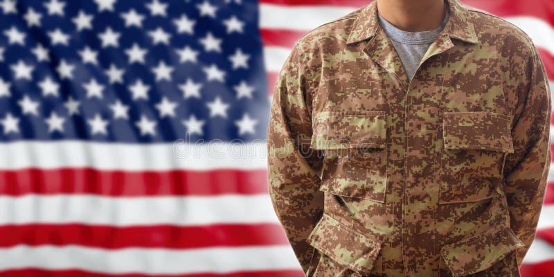 Солдат в американской воинской цифровой форме картины, стоя на предпосылке флага США стоковое изображение rf