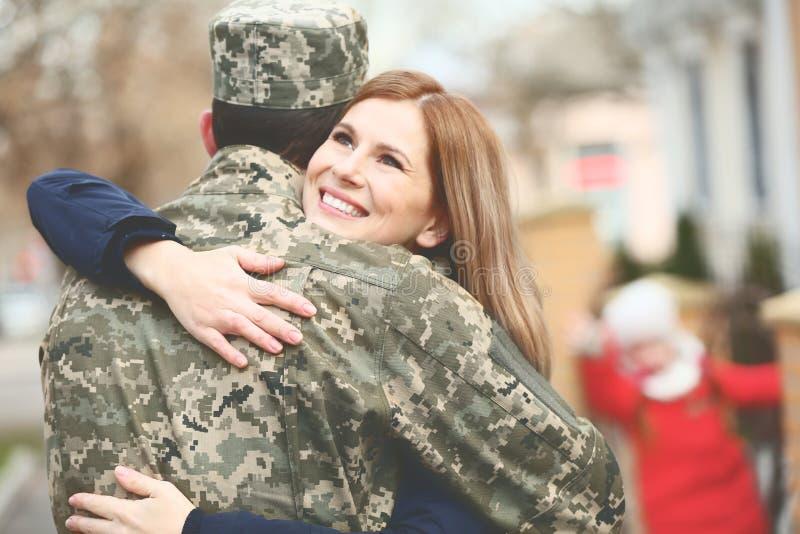 Солдат в камуфлировании обнимая его жену стоковая фотография