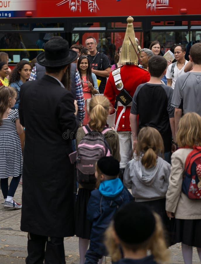 Солдат королевского полка конной гвардии в Лондоне, окруженный туристами включая еврейскую семью в переднем плане стоковая фотография