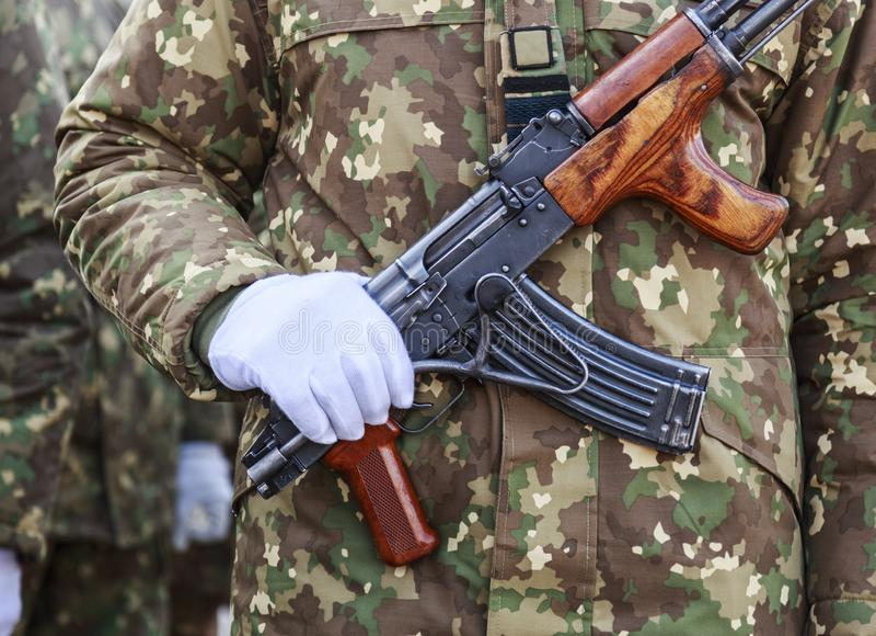 Солдат одетый в белой перчатке с его рукой на оружие стоковое фото rf