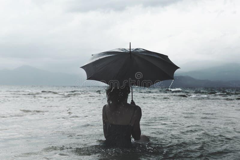 Солитарная женщина с зонтиком ждать шторм в море стоковое фото rf