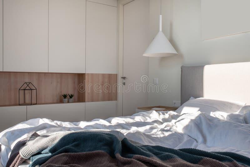 Солнечная современная спальня с белыми стенами и вися лампой стоковые фотографии rf