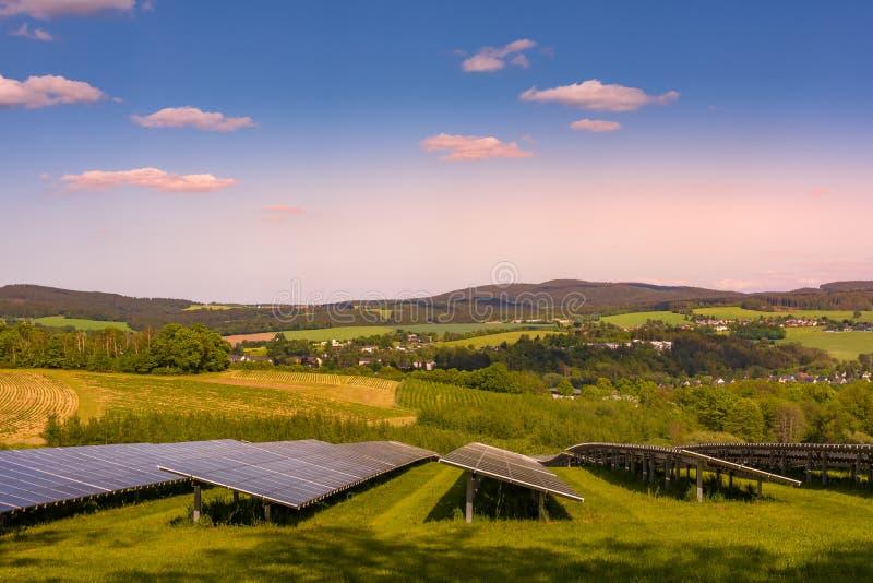 Солнечная ферма с фотовольтайческими панелями на заходе солнца стоковые фотографии rf