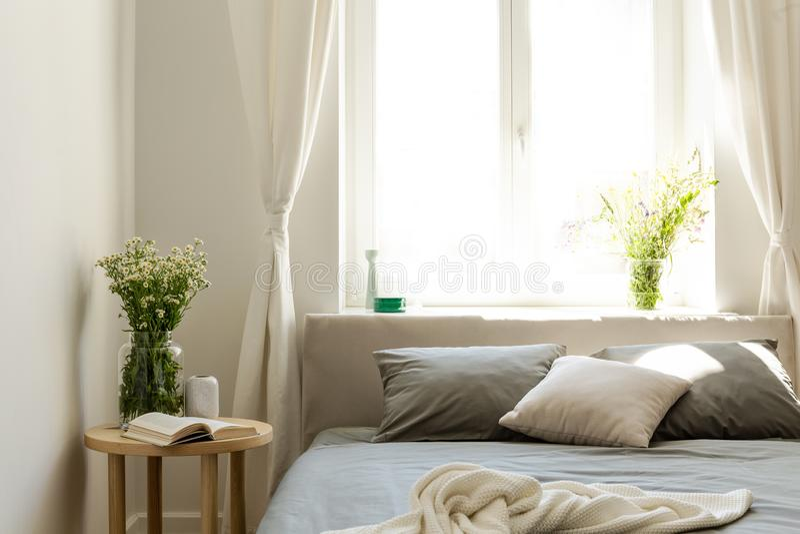 Солнечное утро в естественном интерьере спальни стиля с кроватью, таблицей ночи и пуком полевых цветков Большое яркое окно в стоковое изображение