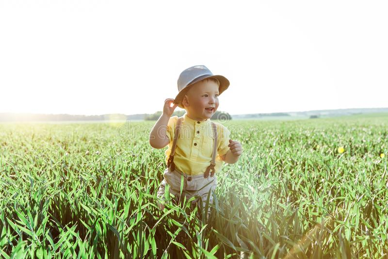 Солнечное фото мальчика на поле малый мальчик в деревне играя в траве и усмехаться стоковое фото