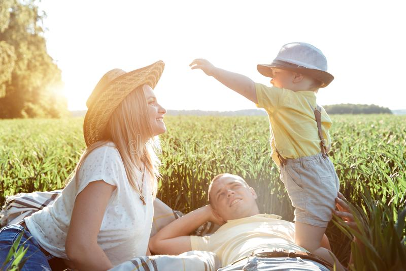 Солнечные изображения счастливой семьи с малым ребенком Родители и сын отдыхают вне города на открытом воздухе стоковые фото
