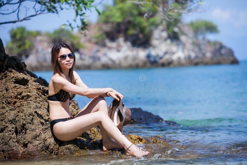 Солнечные очки азиатской женщины нося в бикини ослабляя на пляже стоковые изображения
