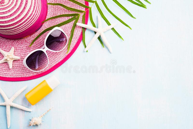 Солнечные очки аксессуаров пляжа, морские звёзды, шляпа пляжа и раковина моря на песчаном пляже и голубая деревянная предпосылка  стоковые фотографии rf